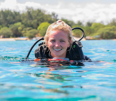 Smiling divemaster on the surface after a dive